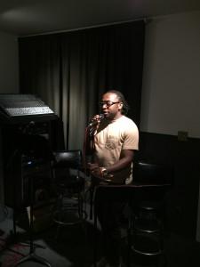 Aimua standing in spotlight singing